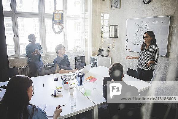 Geschäftsfrau erklärt Kollegen bei Treffen im Kreativbüro die Geschäftsstrategie
