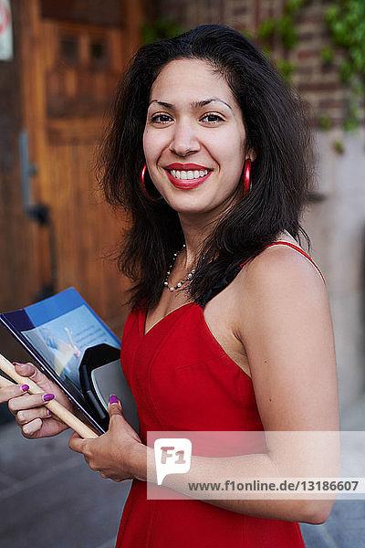 Porträt einer lächelnden jungen Frau mit Buch vor der Sprachschule stehend