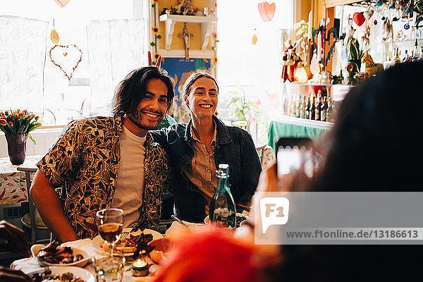 Junge Frau fotografiert lächelnde Freunde  die während des Brunch am Tisch im Restaurant sitzen