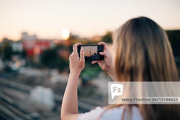 Junge Frau fotografiert Fernsehturm bei Sonnenuntergang mit einem Smartphone