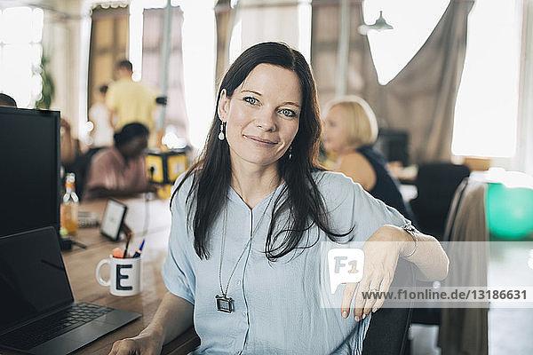 Porträt einer selbstbewussten Geschäftsfrau  die am Schreibtisch im Kreativbüro sitzt