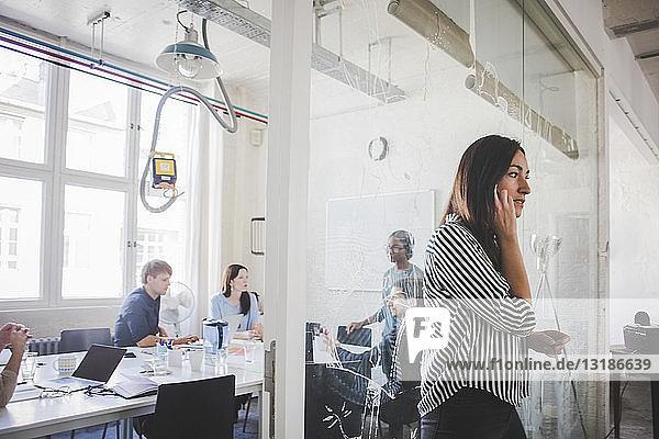Geschäftsfrau spricht am Mobiltelefon  während Kollegen im Sitzungssaal diskutieren