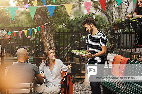 Smiling young woman talking with male friend carrying food during garden party