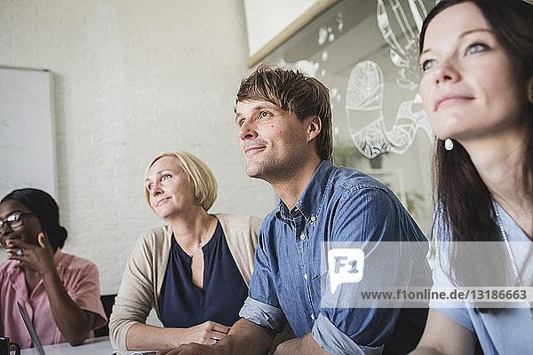 Selbstbewusste kreative Geschäftsleute  die während einer Sitzung im Sitzungssaal sitzen und zuhören