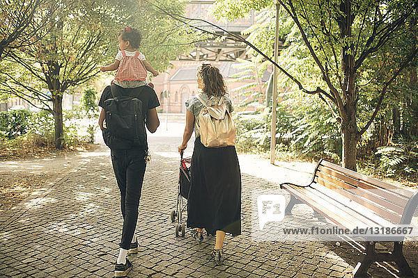 Rückansicht eines Mannes  der seine Tochter auf den Schultern trägt  während eine Frau einen Kinderwagen am Fussweg schiebt