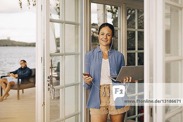 Porträt einer reifen Frau mit Mobiltelefon und Laptop mit Mann im Hintergrund