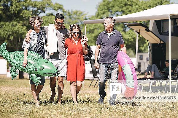 Glückliche Familie mit aufblasbaren Ringen  die in Wohnwagen auf Grasfeld spazieren gehen