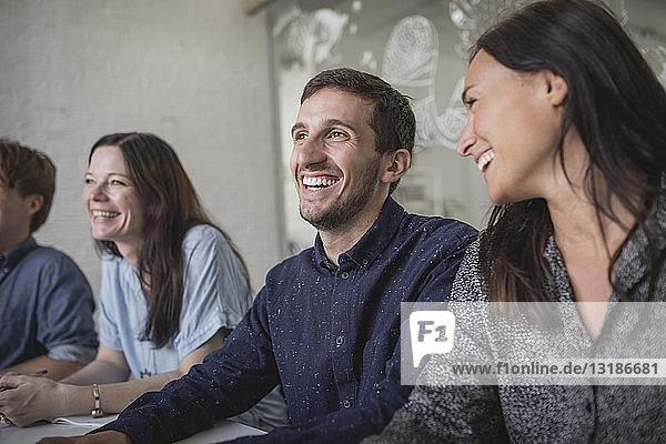 Lächelnde Geschäftsleute hören zu  während sie während der Sitzung im Sitzungssaal sitzen