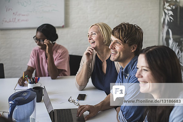 Creative business people smiling while sitting at conference table in board room