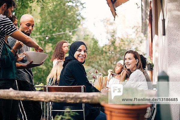 Porträt einer jungen Frau  die während einer Party mit Freunden auf dem Balkon sitzt