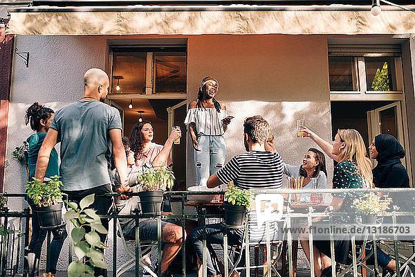 Multiethnische Freunde genießen während einer Party auf dem Balkon