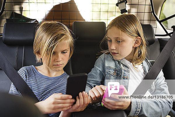 Blonde Geschwister benutzen Smartphones  während sie im Auto sitzen