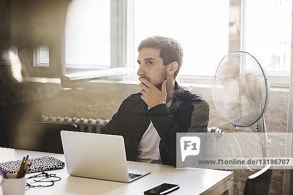 Geschäftsmann hört zu  während er während einer Geschäftsbesprechung im Konferenzraum sitzt