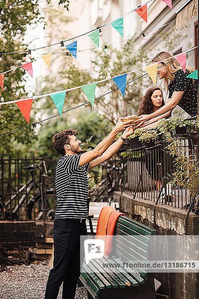 Junge Frau gibt lächelnden männlichen Freund während Gartenparty vom Balkon aus Essen