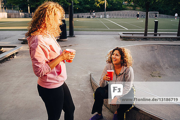 Smiling young women talking while having drinks at skateboard park