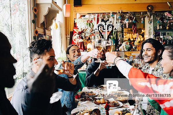 Junge multiethnische Freunde genießen es  bei Tisch im Restaurant anzustoßen