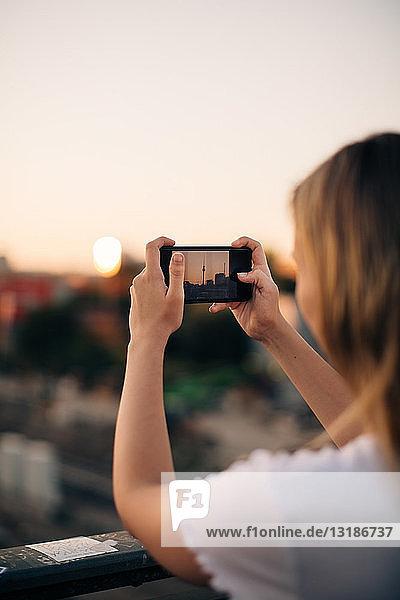 Ausschnitt einer jungen Frau  die bei Sonnenuntergang mit einem Smartphone den Fernsehturm fotografiert