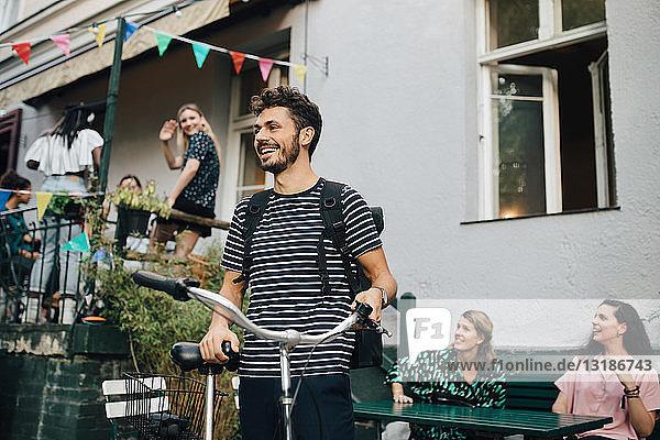 Lächelnder junger Mann steht mit Fahrrad im Hinterhof
