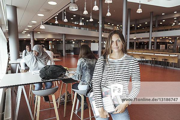Porträt einer Universitätsstudentin  die in der Cafeteria mit Freunden im Hintergrund steht