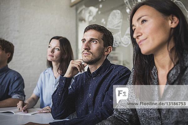 Kreative Geschäftsleute hören zu  während sie während einer Sitzung im Sitzungssaal sitzen