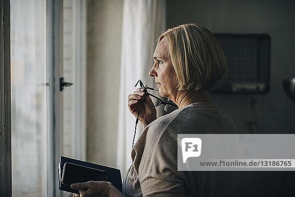 Reife Geschäftsfrau spricht über Kopfhörer  während sie im Kreativbüro am Fenster steht
