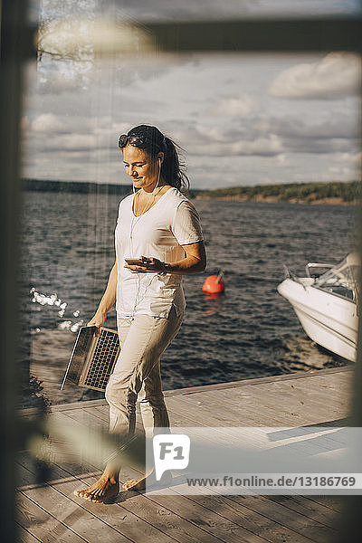 Full length of woman with mobile phone and laptop walking on patio by lake