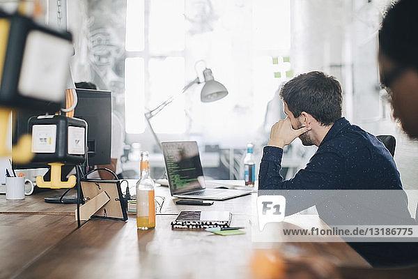 Männlicher Computerprogrammierer am Schreibtisch im Kreativbüro