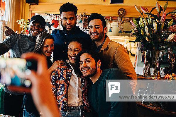 Junge Frau fotografiert fröhliche multi-ethnische Freunde  die während des Brunch im Restaurant stehen