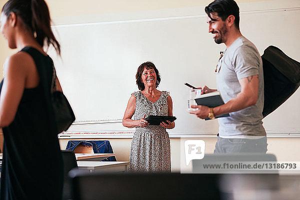 Ältere Frau lächelt  während sie ein digitales Tablet im Klassenzimmer hält
