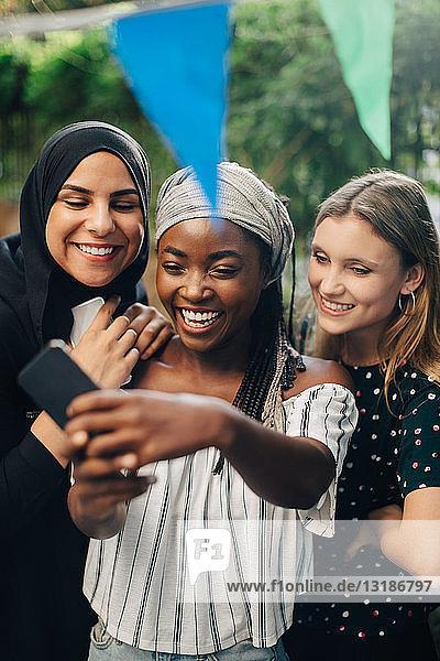 Glückliche multiethnische Freundinnen  die sich über ein Smartphone im Garten selbstständig machen