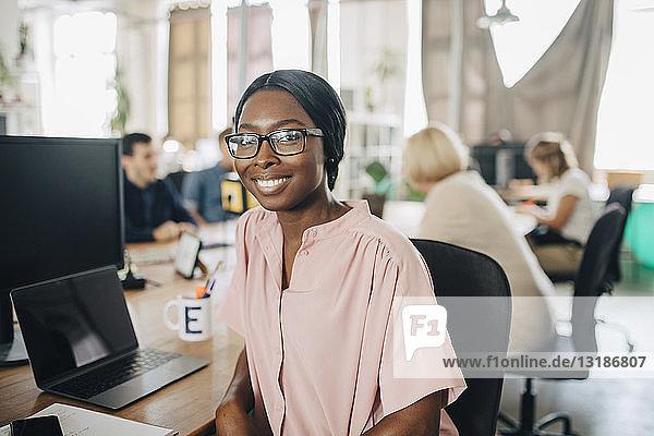 Porträt einer lächelnden jungen Geschäftsfrau  die in einem kreativen Büro am Schreibtisch sitzt