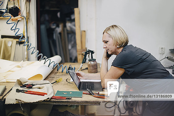 Side view of mature female upholstery worker looking at laptop while talking on phone in workshop