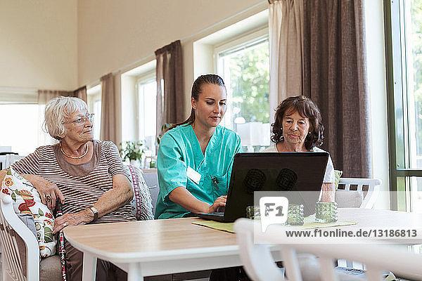 Young nurse using laptop while sitting amidst senior women at nursing home