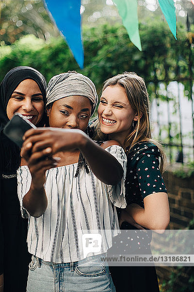 Fröhliche multiethnische Freundinnen  die sich im Hinterhof per Mobiltelefon selbstständig machen