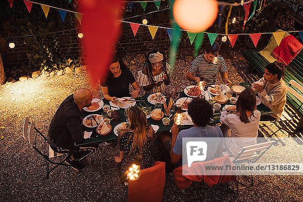 Schrägansicht auf multi-ethnische Freunde beim Abendessen während einer Gartenparty im Garten