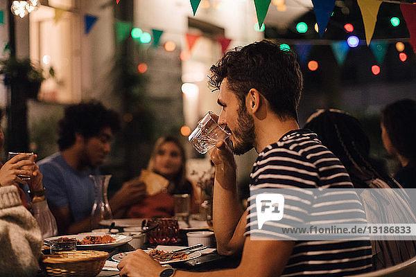 Junger Mann trinkt Wasser  während er während einer Gartenparty mit Freunden zu Abend isst