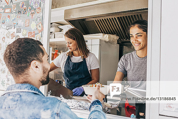 Smiling young female owner giving bowl of Tex-Mex to male customer from food truck