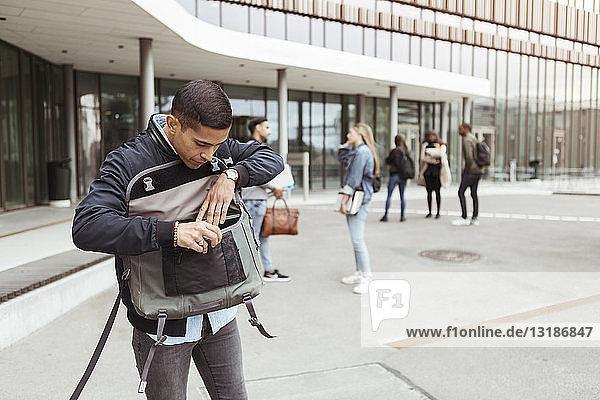 Junge Studentin sucht in Tasche  während Freunde an der Universität im Hintergrund stehen