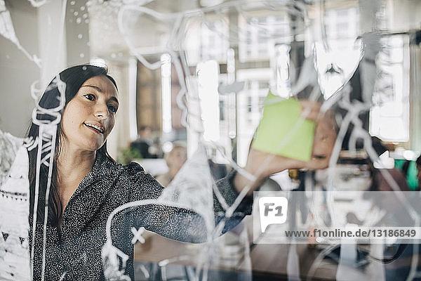 Geschäftsfrau klebt Klebezettel auf gemustertes Glas im Kreativbüro