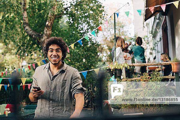 Porträt eines jungen Mannes mit Handy in der Hand im Hinterhof