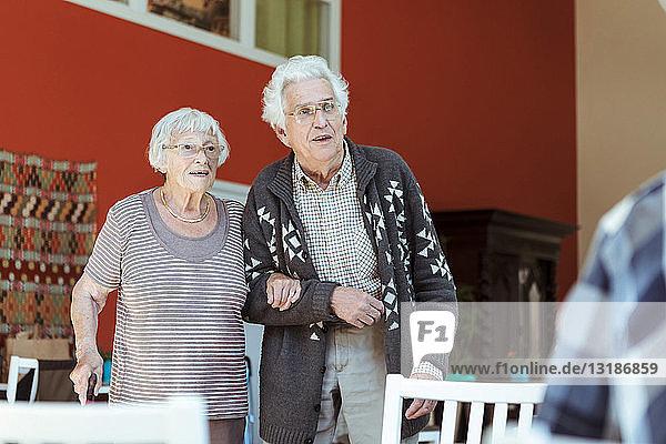 Älteres Ehepaar steht Arm in Arm im Pflegeheim