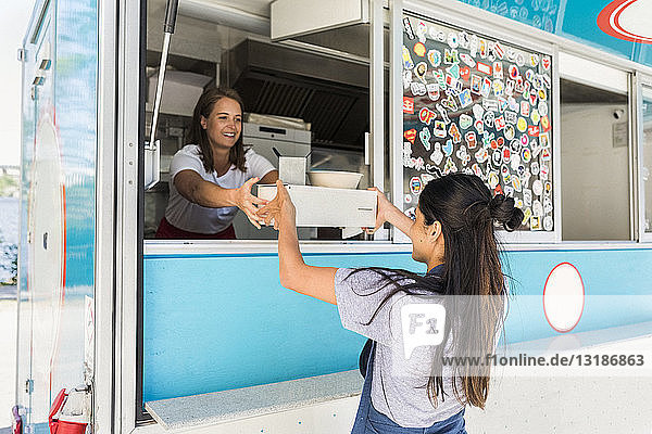 Lächelnde junge multiethnische Besitzerin übergibt Container an Verkäuferin am Speisewagen