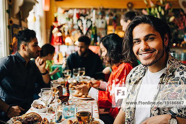 Porträt eines lächelnden jungen Mannes  der mit multi-ethnischen Freunden zusammensitzt und eine Dinnerparty im Restaurant genießt