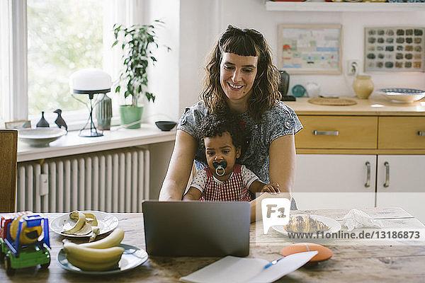 Lächelnde Frau mit Laptop  während sie mit ihrer Tochter am Esstisch im Haus sitzt