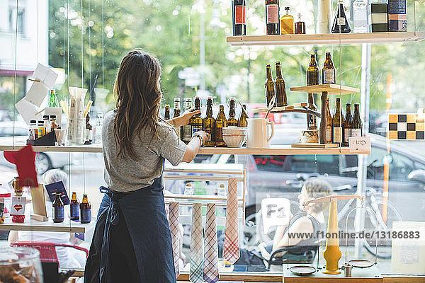 Rear view of female employee arranging bottles on shelf in deli