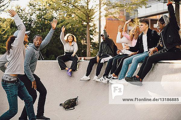 Freunde tanzen mit erhobenen Händen im Skateboard-Park
