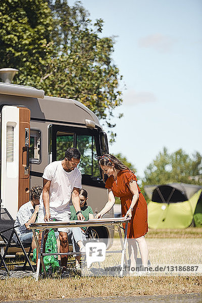 Parents arranging table while siblings sitting against van at trailer park during summer
