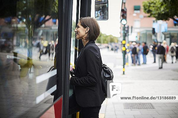 Seitenansicht einer lächelnden Geschäftsfrau  die in der Stadt in den Bus steigt