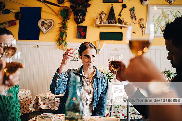 Junge Frau hebt einen feierlichen Toast aus  während sie mit multiethnischen Freunden bei einer Dinnerparty im Restaurant sitzt