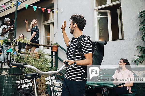 Lächelnder junger Mann winkt mit der Hand  während er mit dem Fahrrad im Hinterhof steht